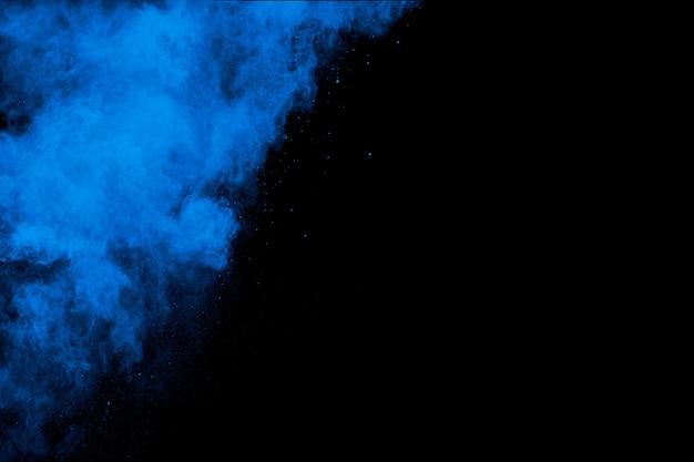 Bizarre vormen van blauwe poeder explosie wolk op witte achtergrond. gelanceerde blauwe stofdeeltjes spatten.