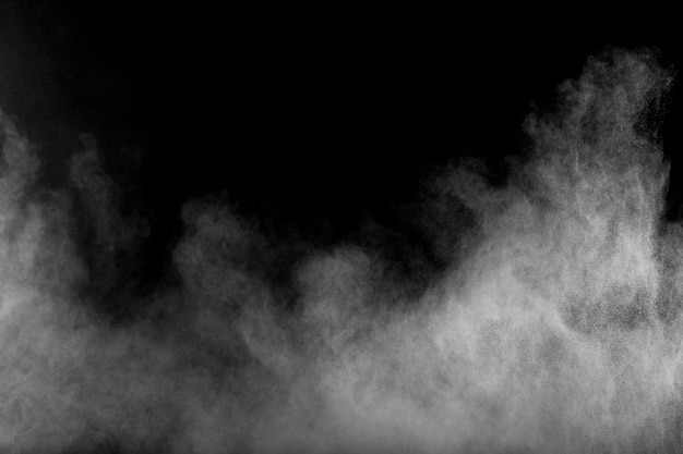 Bizarre vormen van de witte wolk van de poederexplosie tegen zwarte achtergrond. de witte stofdeeltjes bespatten.