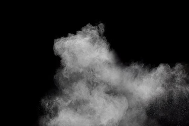 Bizarre vormen van de witte wolk van de poederexplosie tegen zwarte achtergrond