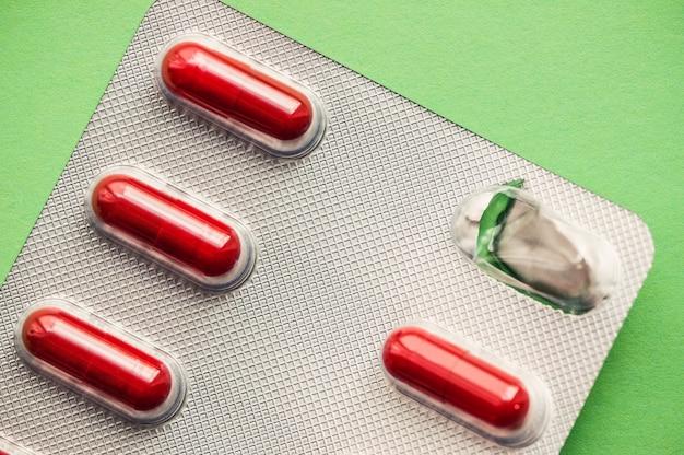Blaar heldere rode tabletten op een groene achtergrond.