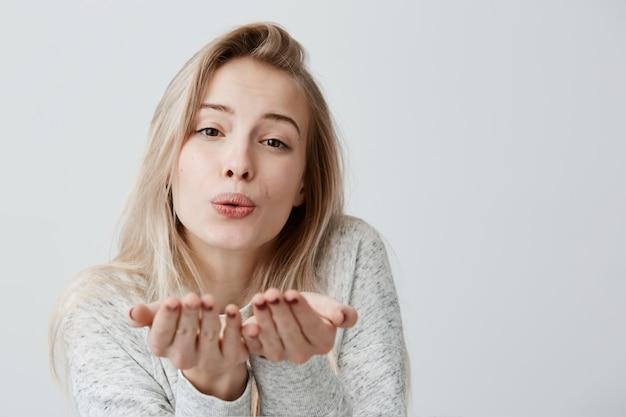Blaast de blonde aantrekkelijke vrouwelijke vrouw kus