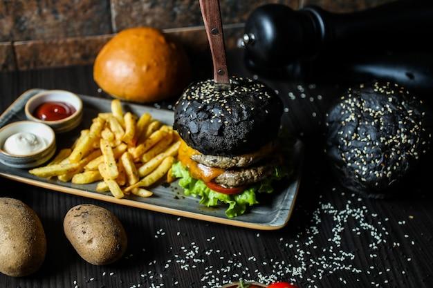 Black beef burger met ingrediënten en frietjes