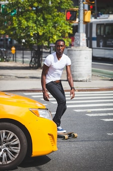 Black boy skating met longboard on the road