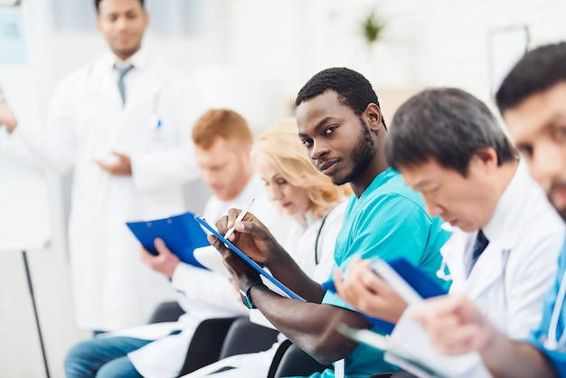 Black doctor camera staring tijdens de lezing.