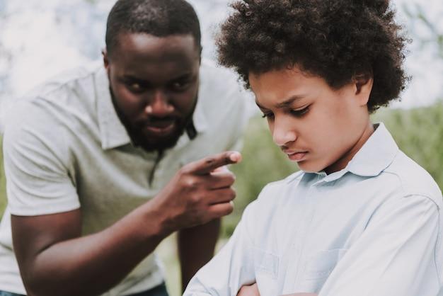 Black father scolds son and boy draaide zich van hem af