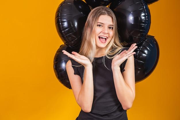 Black friday-concept met blonde aantrekkelijke vrouw met mooie opgewonden, in het zwart gekleed kijkt naar camerastands met zwarte luchtballonnen gele achtergrond, kopieer ruimte.