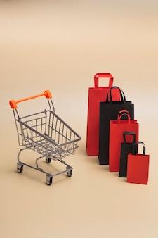 Black friday concept, mockup van papieren zwarte en rode boodschappentassen met trolley op gekleurde achtergrond. black friday-uitverkoop. verticale foto