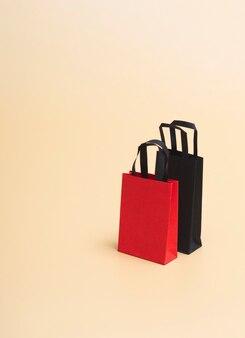 Black friday concept, mockup van papieren zwarte en rode pakketten op gekleurde achtergrond. zwarte vrijdag. met kopie ruimte
