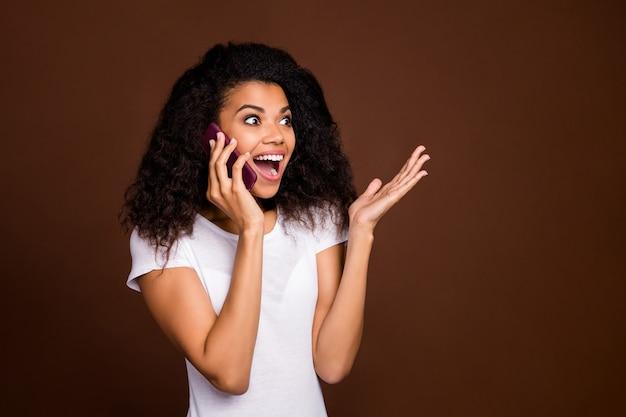 Black friday echt ?! gekke grappige afro-amerikaanse meisje praten vriend gebruik mobiele telefoon hoor geweldig nieuws schreeuw wow omg voel je verheug uitdrukking draag wit t-shirt.