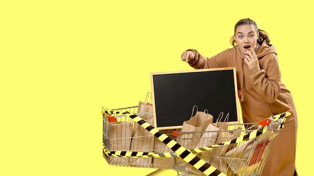 Black friday, het meisje wijst verbaasd naar het bordje in het winkelmandje