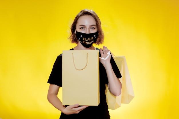 Black friday-uitverkoop. vrouw in gezichtsmasker met black friday-boodschappentassen in handen. verkoop tijdens pandemie.