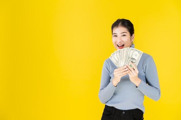 Black friday-verkoop advertentiebanner portret van aziatische gelukkige vrouwen die geld in een gelukkig gebaar houden