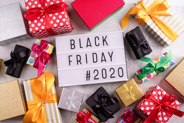 Black friday-verkoop tekst op een lightbox met verschillende geschenkdozen