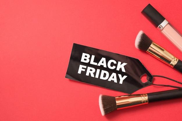 Black friday-verkoop van schoonheidsmiddelen op rode achtergrond met een exemplaarruimte