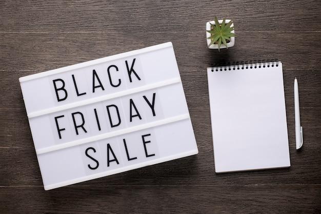 Black friday-verkoopbericht op lightbox op een houten bureau