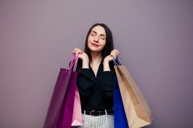 Black friday-verkoopconcept voor de winkel. winkelende vrouw die in zonnebril zak houden die op donkere oppervlakte wordt geïsoleerd.