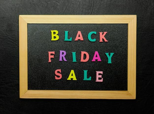 Black friday-verkoopteken op brievenraad over zwarte achtergrond