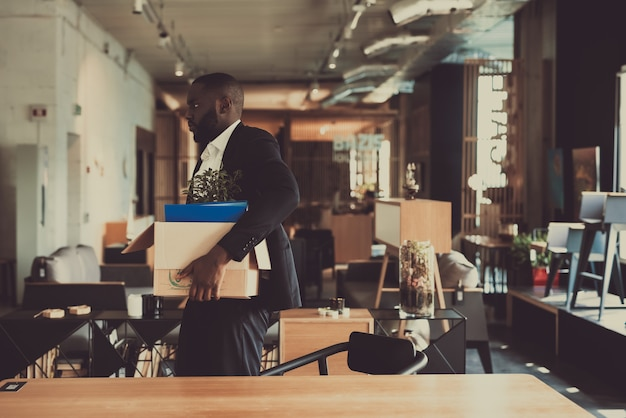 Black manager verlaat werkplek met office box.