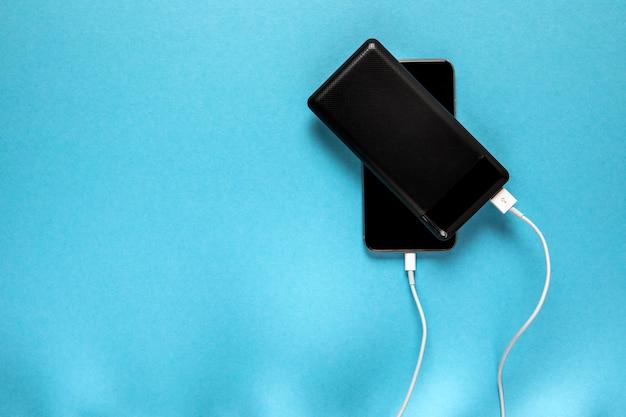 Black power bank laadt smartphone geïsoleerd