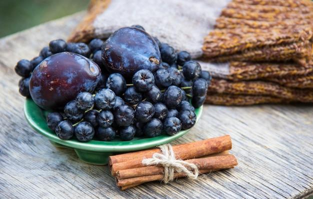 Black rowan en pruimen op houten tafel.