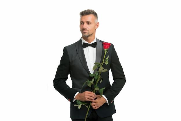 Black tie dresscode voor avondevenementen. smoking man met roze bloem. fijne valentijnsdag. speciale gelegenheid. mannelijke formele kledingstijl. knappe man zwart smoking pak. sexy man op romantische date.
