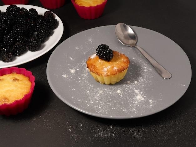 Blackberry-muffins met poedersuiker en verse bessen.