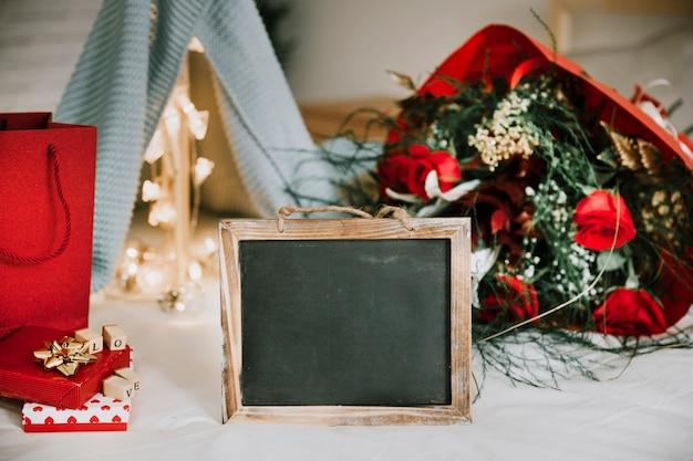 Blackboard in de buurt van bloemen en geschenkdozen