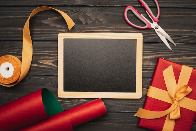 Blackboard mock-up met inpakpapier en cadeau voor kerst