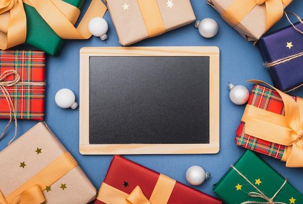 Blackboard mock-up met kerstcadeautjes Gratis Foto