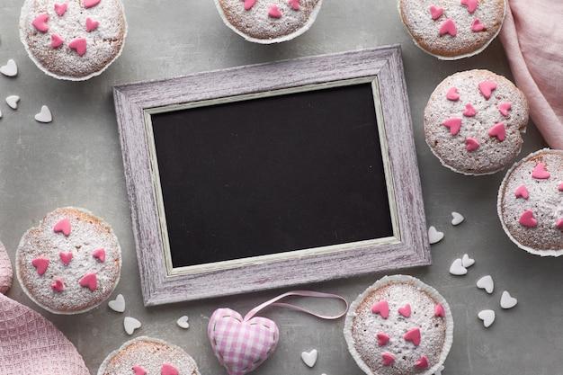 Blackboard omlijst met suiker bestrooide muffins met roze en witte fondant glazuur harten