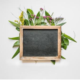 Blackboard op bladeren en bloemen