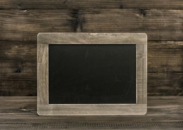 Blackboard schoolbord op houten achtergrond. vintage textuur met kopie ruimte voor uw tekst