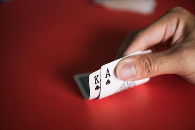 Blackjack kaarten in handen op rode tafel