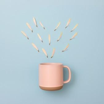 Blad array hart vorm en roze koffiekopje op blauwe achtergrond. valentijnsdag concept