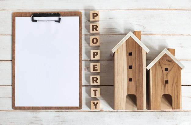 Blad op klembord met woord eigendom op houten alfabetblokken en huismodellen