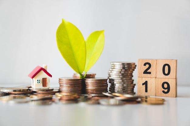 Blad op stapelmunten met minishuis en jaar 2019 gebruikend als financiële groei en bedrijfsconcept
