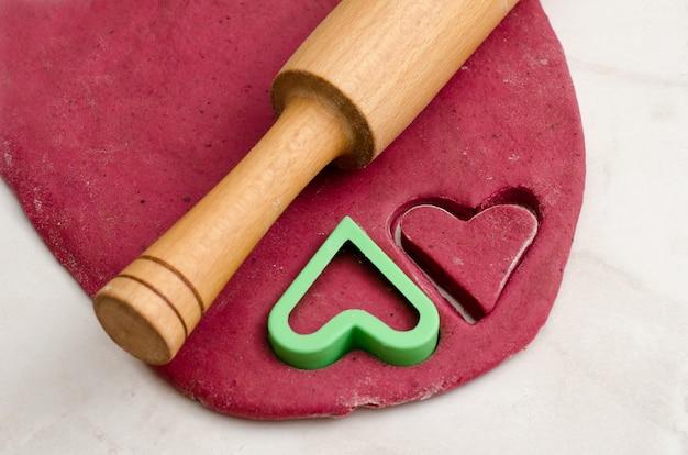 Blad rood deeg met een deegrol en koekjessnijdershart, dat zich op valentijnsdag voorbereidt