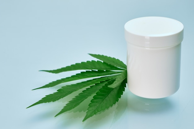 Blad van cannabis en plastic verpakking of pot met kopie ruimte met biologische room bevatte hennepolie op de blauwe achtergrond. productie van cosmeticaproducten voor huidverzorging.