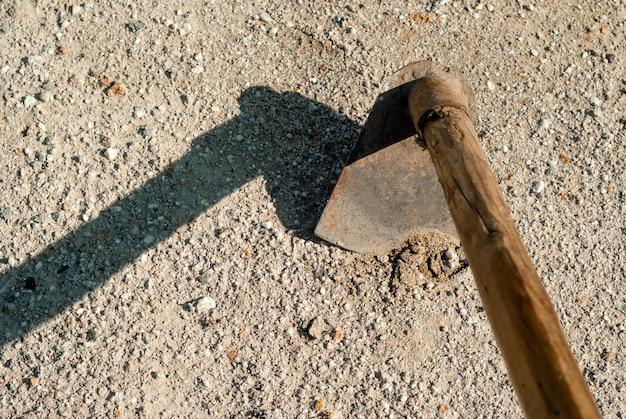 Blad van een primitieve schoffel, die droge harde kale zandgrond probeert te doorboren