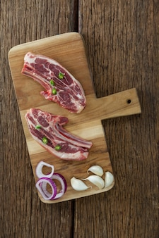 Blade chop, uien en knoflook op een houten bord