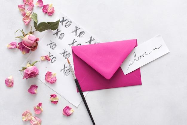 Bladen met titels, penseel, envelop en bloemen