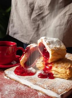 Bladerdeeg dessert rode jam hand viburnum kersen kopje koffie zwarte achtergrond