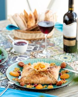 Bladerdeeg khachapuri en een glas rode wijn
