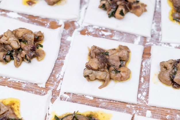 Bladerdeeg met kip die voor baksel voorbereidingen treft