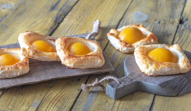 Bladerdeeg met perziken in blik op de houten tafel