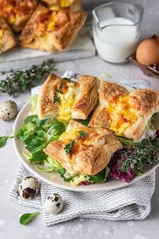 Bladerdeeg mini quiche, taart of taart met groenten geserveerd op een bord met groene mix salade.