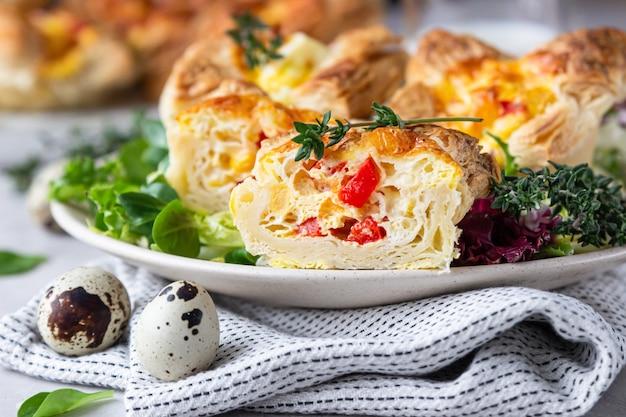 Bladerdeeg mini quiche, taart of taart met groenten geserveerd op een bord met groene mix salade. Premium Foto