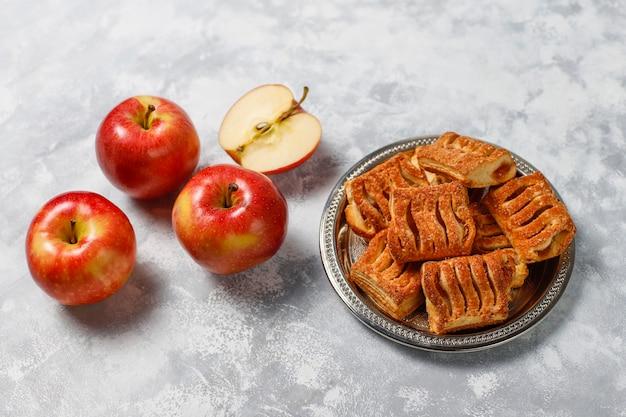 Bladerdeegkoekjes gevuld met appeljam en verse rode appels op licht beton