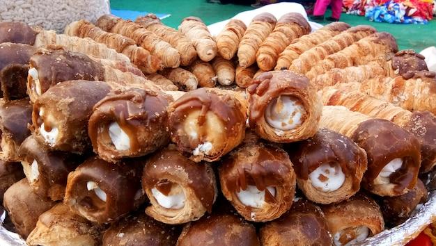 Bladerdeegrolletjes of gebak verkopen op de markt bij lucknow