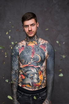 Bladeren die over de hipster jonge man vallen met tatoegering op zijn lichaam die zich tegen grijze muur bevinden